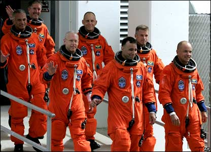 The seven astronauts leaving the Operations and Checkout building for a trip to the launch pad.