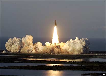 The solid rocket boosters on the space shuttle Atlantis light up ponds during lift-off