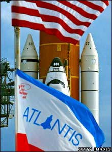 Flags fly near the Space Shuttle Atlantis as it sits on launch pad 39-a in preparation for launch