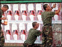 Albanian soldiers put up posters