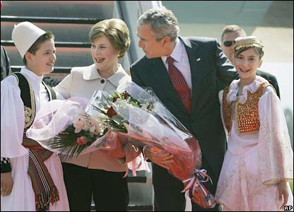 US President George W Bush and his wife, Laura, talk to children dressed in Albanian national costumes in Tirana