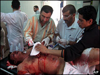 Medics help a man wounded in a police station bombing near Tikrit on 10 June 2007