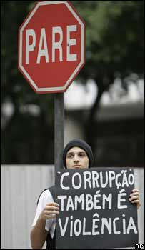 "A man holds a banner that reads in Portuguese ""Corruption is also violence"" during a protest against violence in Rio de Janeiro on 31 May 2007"