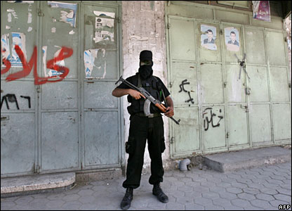 A Hamas militant stands in front of closed shops in Gaza City