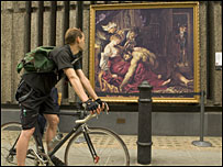 A man stops to look at a painting on display