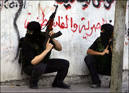 Palestinian militants from Hamas take cover during a gun battle with Fatah militants in Gaza City