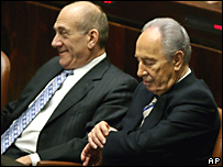 Shimon Peres revisa su reloj mientras espera el resultado de la votación. A su derecha, el premier israelí Ehud Olmert.