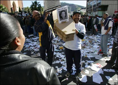 Protesters carry a mock coffin of the country's public service minister in Cape Town, South Africa