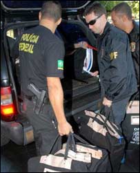 Federal police agents handle investigation documents. Photo courtesy: Wilson Dias - Agencia Brasil