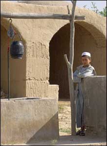A boy standing next to a water pump