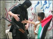 Un niño palestino saluda a un combatiente de Hamas.