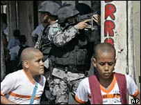 Two boys walk past police officers in the Complexo de Alemao shanty town