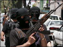 Masked Palestinian police officers patrol the streets of the West Bank town of Hebron (14 June 2007)