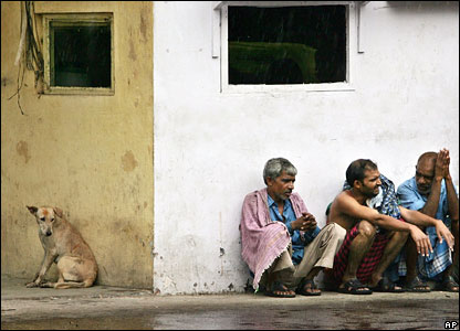 Dog and men shelter from rain in New Delhi, India