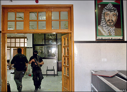 Hamas militants and a portrait of former Palestinian leader Yasser Arafat
