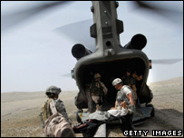 British medics carrying a wounded man onto a Chinook helicopter