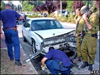 Israeli soldiers look at the wrecked car in Kiryat Shmona.