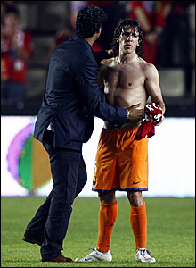 Barcelona coach Frank Rijkaard consoles captain Carlos Puyol after they lose the league title race to rivals Real Madrid