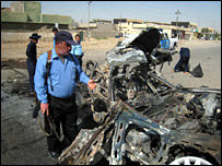 Iraqi police with bombed out car
