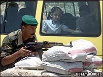 Un guardia de Fatah con un bus escolar de fondo en la ciudad de Naplusa