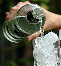 Vodka being poured into an ice-filled glass
