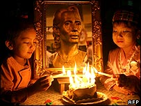 Children lighting birthday cake candles in front of Aung San Suu Kyi portrait