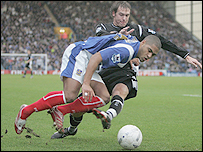 Andreas Granqvist (in black) tackles Portsmouth's Glen Johnson during his one outing for Wigan during his loan spell at the JJB Stadium club