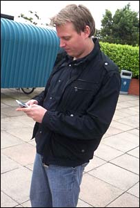 Ian Walker, BBC News reporter, tests a mobile phone