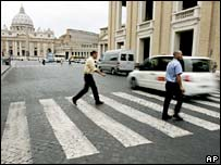 Pedestrians cross a street as motorists drive past St Peter's square in Rome