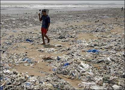 A beachgoer walks through rubbish littering Juhu Beach in Mumbai (Bombay), India