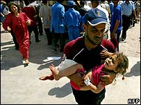 A man rushes a child to hospital after the Amirli bombing