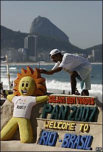 Un escultor de arena termina un modelo de la mascota del torneo, Caue (sol), con un mensaje de bienvenida para los visitantes.