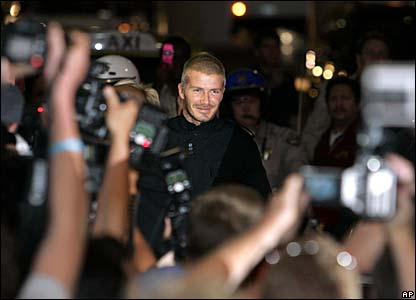 David Beckham is surronded by photographers