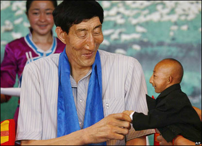 The world's tallest man, China's Bao Xishun, at 2.36 meters (7ft 9in), shakes hands with the man hoping to be officially declared the shortest, He Pingping, 73cm (2ft 5in) tall.