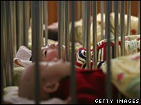 Children in rows of cots in a Chinese orphanage