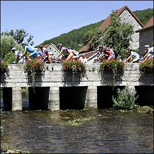 The riders cross a bridge on stage six