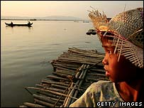 A Burmese girl waits for her father's boat to come to shore along the Ayeryarwady river  in Mandalay in February 2007.