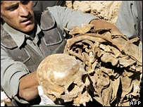 A policeman displays human remains found at the mass grave (photo: Massoud Hossaini)