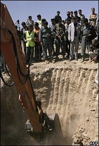 Afghan officials watch as a digger unearths the mass grave (photo: Massoud Hossaini)