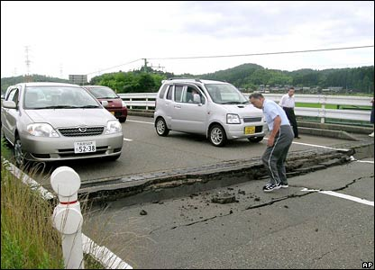 People look at a damaged road in Kariwa village, Niigata prefecture