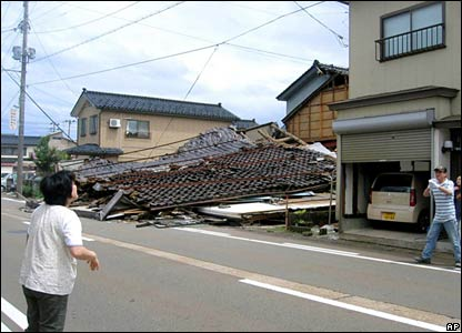 A passer-by looks at a collapsed house in Kashiwazaki