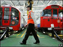 Worker walking past Tube trains