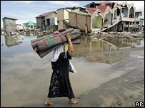 Woman walks past houses destroyed by Asian tsunami