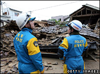 Police pass by a collapsed house in Kashiwazaki
