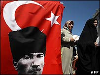 Women pass a Turkish flag with a picture of Mustafa Kemal Ataturk