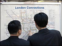 Two men looking at a tube map
