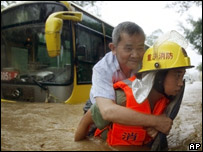 A Chinese rescue worker helps an elderly resident through flood waters in Chongqing