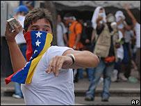 Estudiante con bandera venezolana tapándole la cara, lanza una piedra en una manifestación.