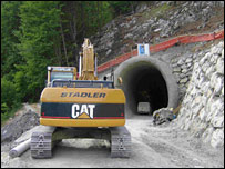 Digger working on road into tunnel