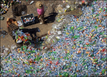 Workers select plastic bottles at a recycle disposal site